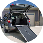 A wheelchair ramp hanging off the back of a SUV