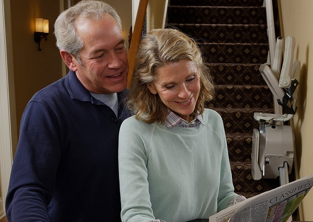 a happy couple reading the newspaper with a stairlift in the background