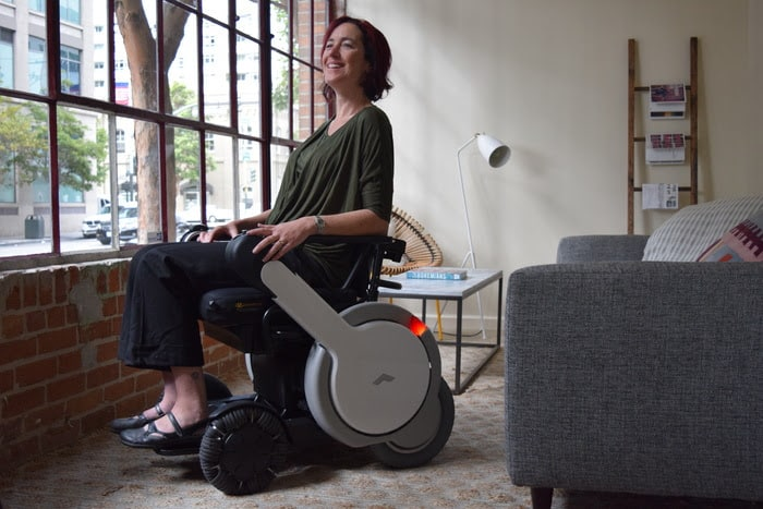 a woman in a wheelchair looking out the window