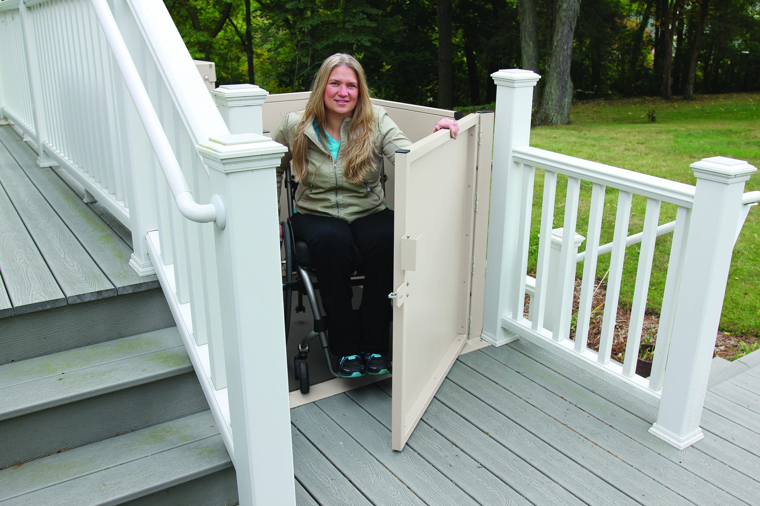 A woman outside using the Bruno Residential Vertical Platform Lift to get up and down stairs in a wheelchair