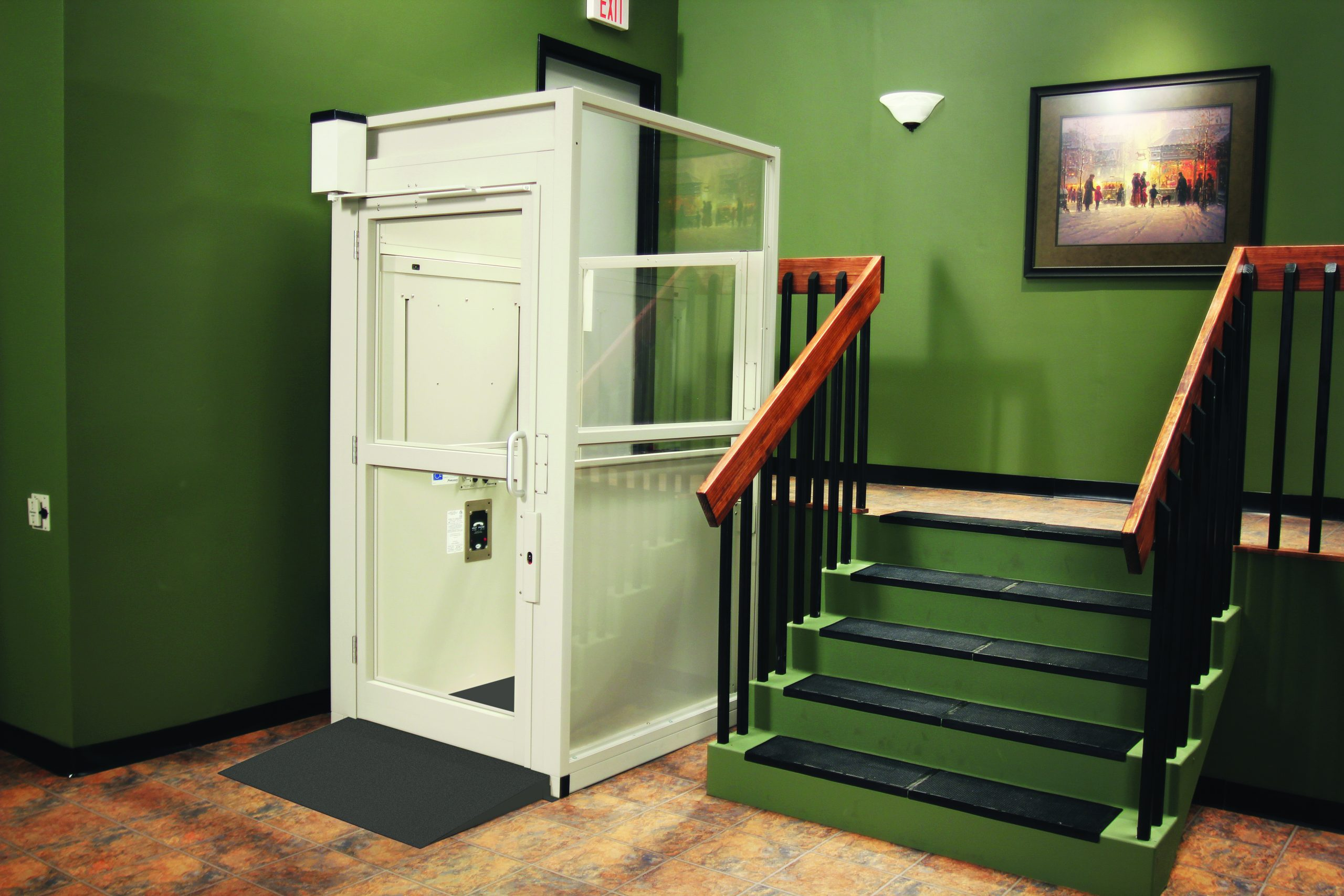 The Bruno Commercial Vertical Platform Lift inside a green room beside stairs