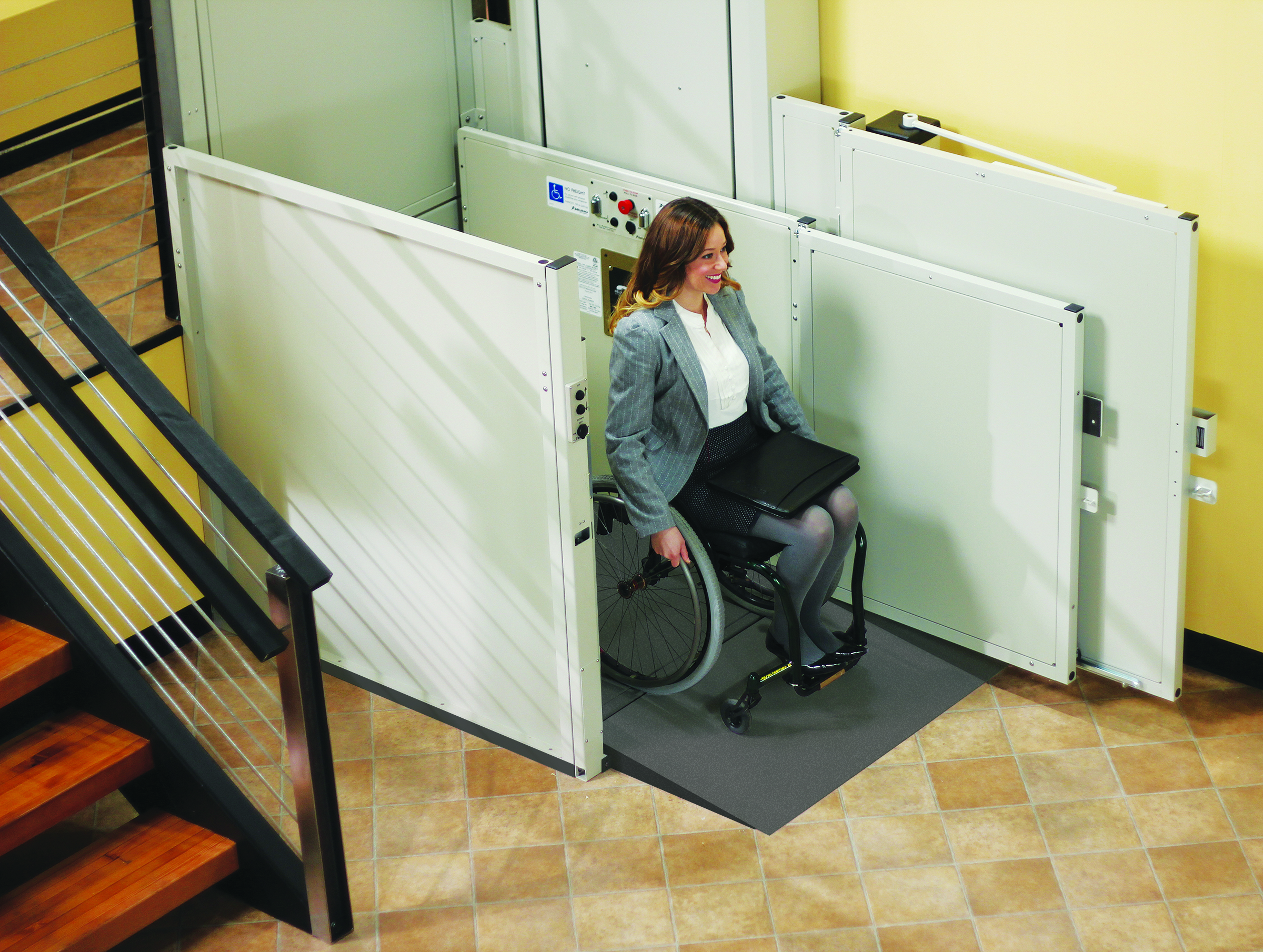 A woman in a wheelchair using the Bruno Commercial Vertical Platform Lift inside