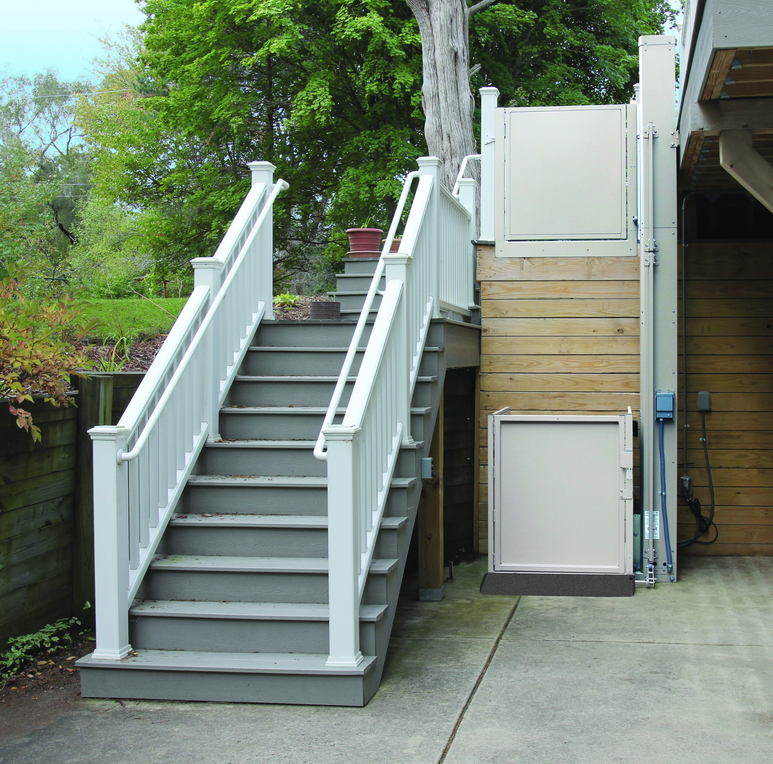 The Bruno Residential Vertical Platform Lift installed beside stairs outside