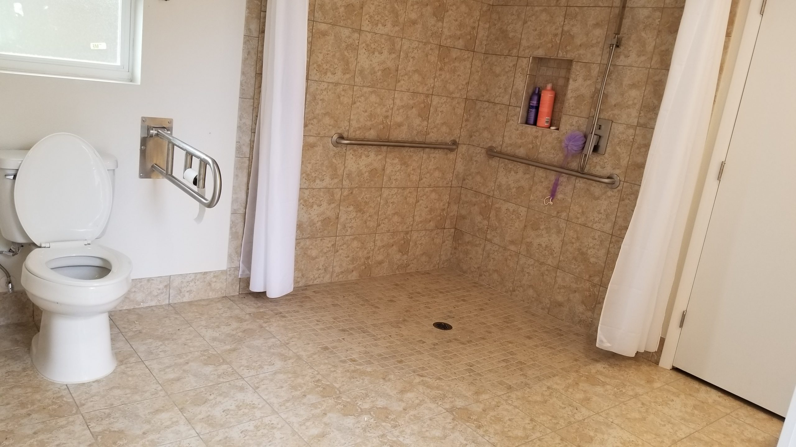 A bathroom with a grab bar installed in the shower