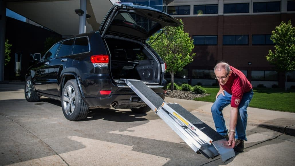 A man setting up a Trifold Advantage Series Ramp leading into a car