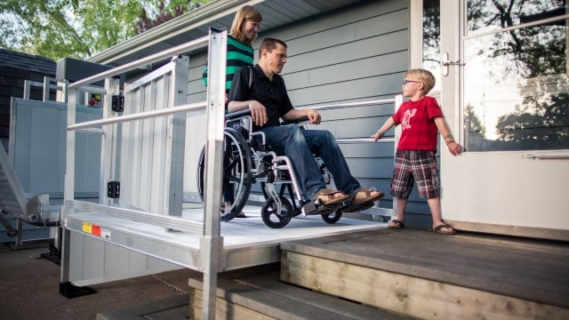 A man in a wheelchair with his wife and son using the EZ-ACCESS PASSPORT® Vertical Platform Lift