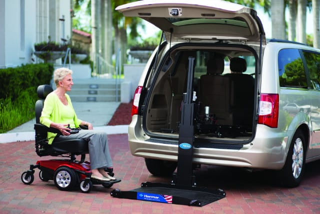 A woman on a scooter using a lift to put get in a van