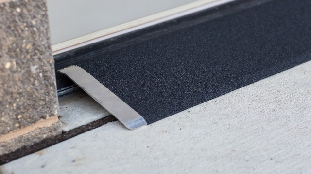 Black angled entry plate in front of a cement entry