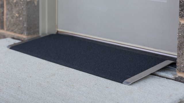 Black angled entry plate in front of a door