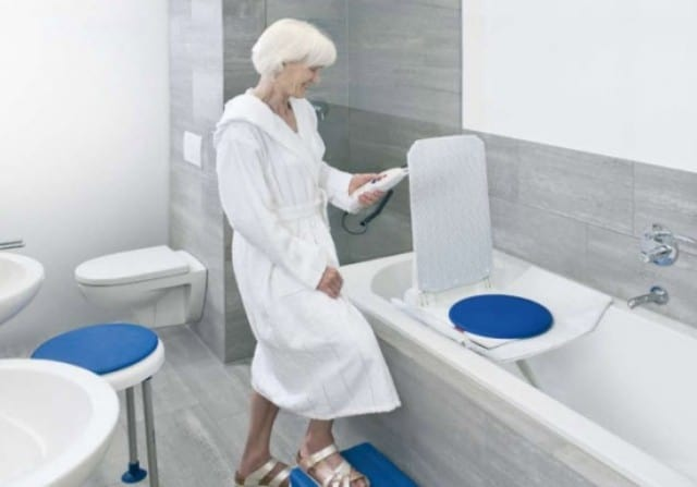 Woman standing beside a bathtub with a bath lift in the tub.
