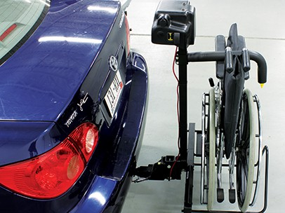A side view of the Bruno Back Saver as it lifts a wheelchair into a car