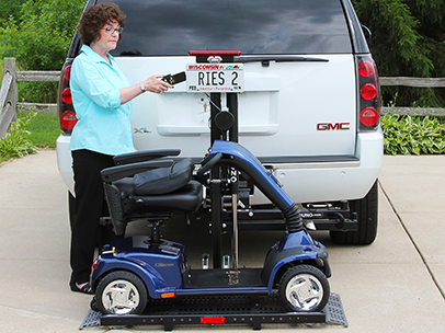A woman using a pull out slider to lift her scooter into a van