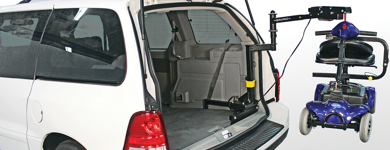 A space saver attached to a van expanded and holding a scooter
