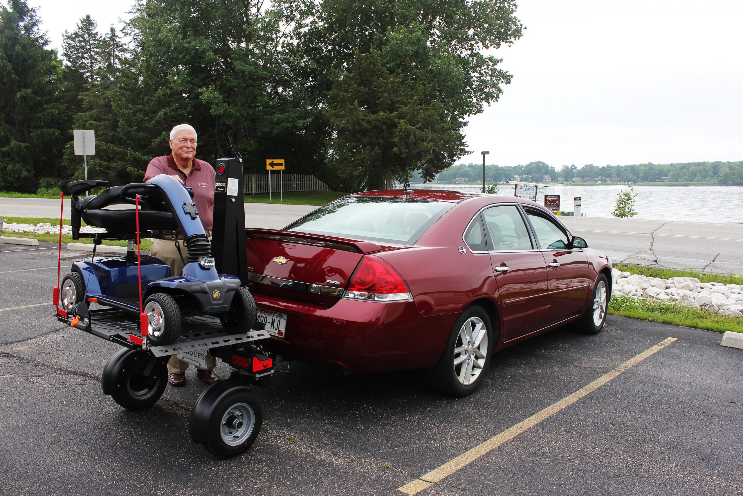 A man standing beside a scooter on a chariot attached to a car