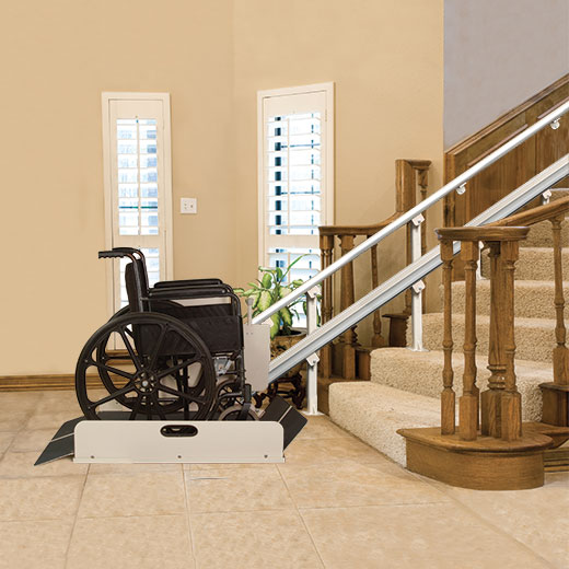 An incline platform with a wheelchair on it leading up stairs inside