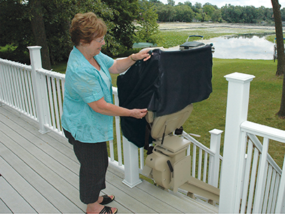 Woman putting cover on outdoor bruno stair lift