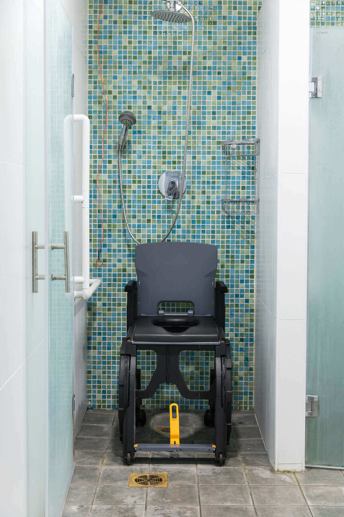 The Seatara WheelAble Toilet and Shower Chair in a shower with green tiles