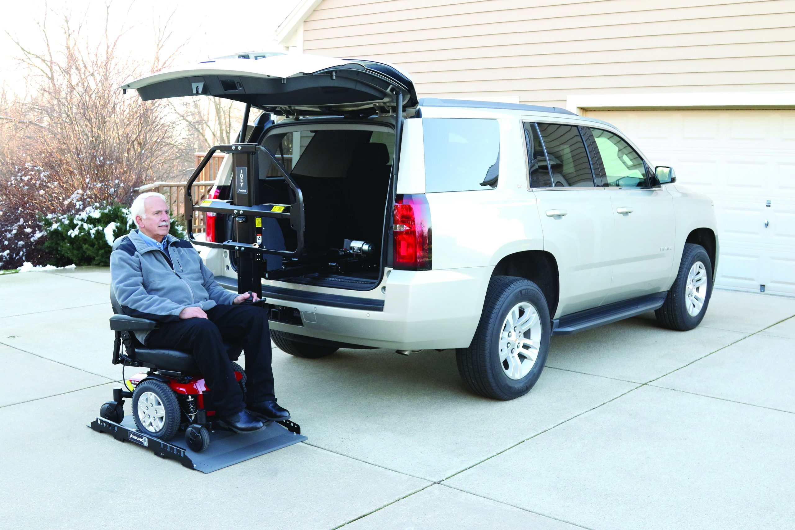 A man in a wheelchair going up a vehicle lift leading into a car