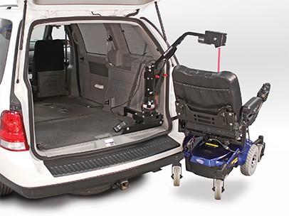 A lifter lifting a wheelchair into a car