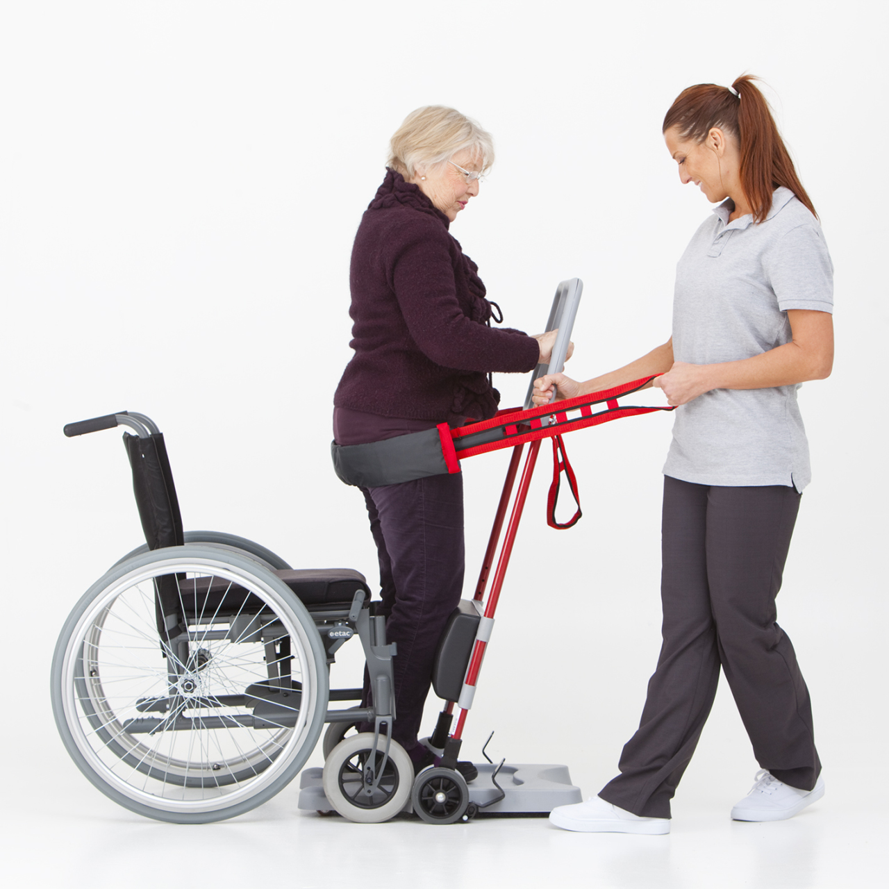 Two woman using a raiser to utilize a wheelchair