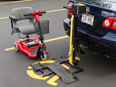 A pull out slider attached to a truck that has a scooter beside it