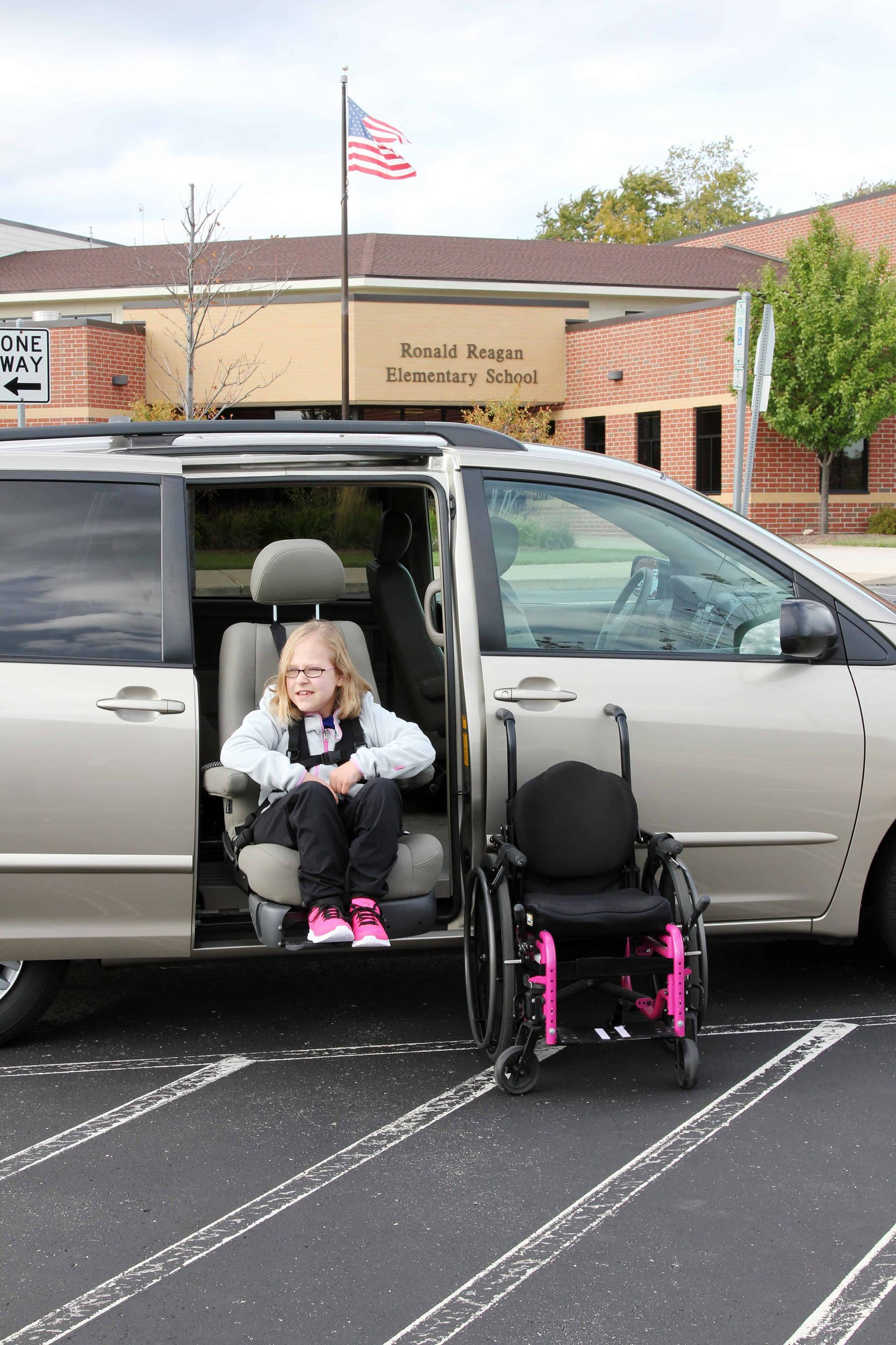 A girl sitting in the Bruno Valet Seat with her wheelchair beside her