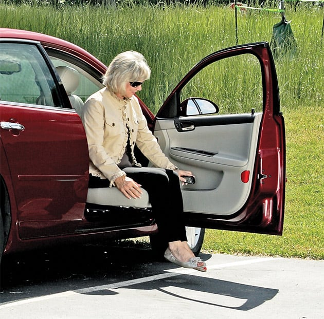 A woman sitting in the Bruno Valet Seat in a red car