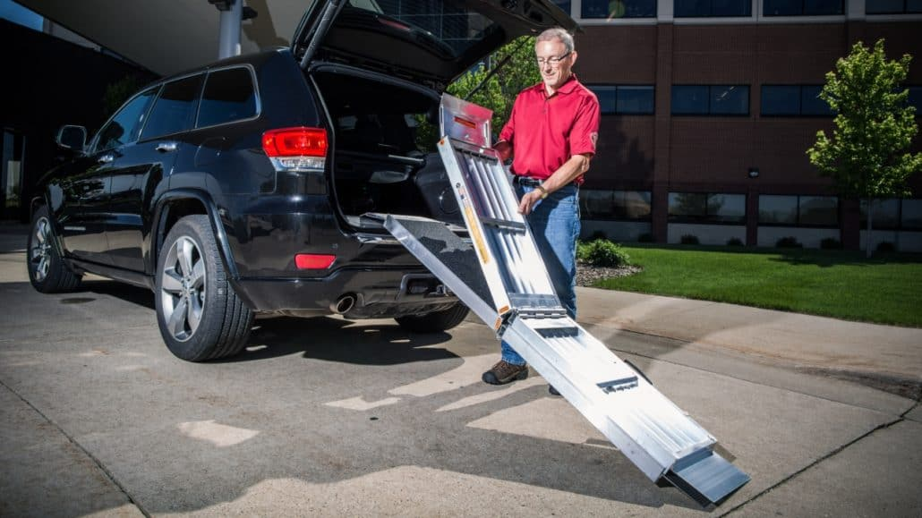 A man folding up a Trifold Advantage Series Ramp leading into a car