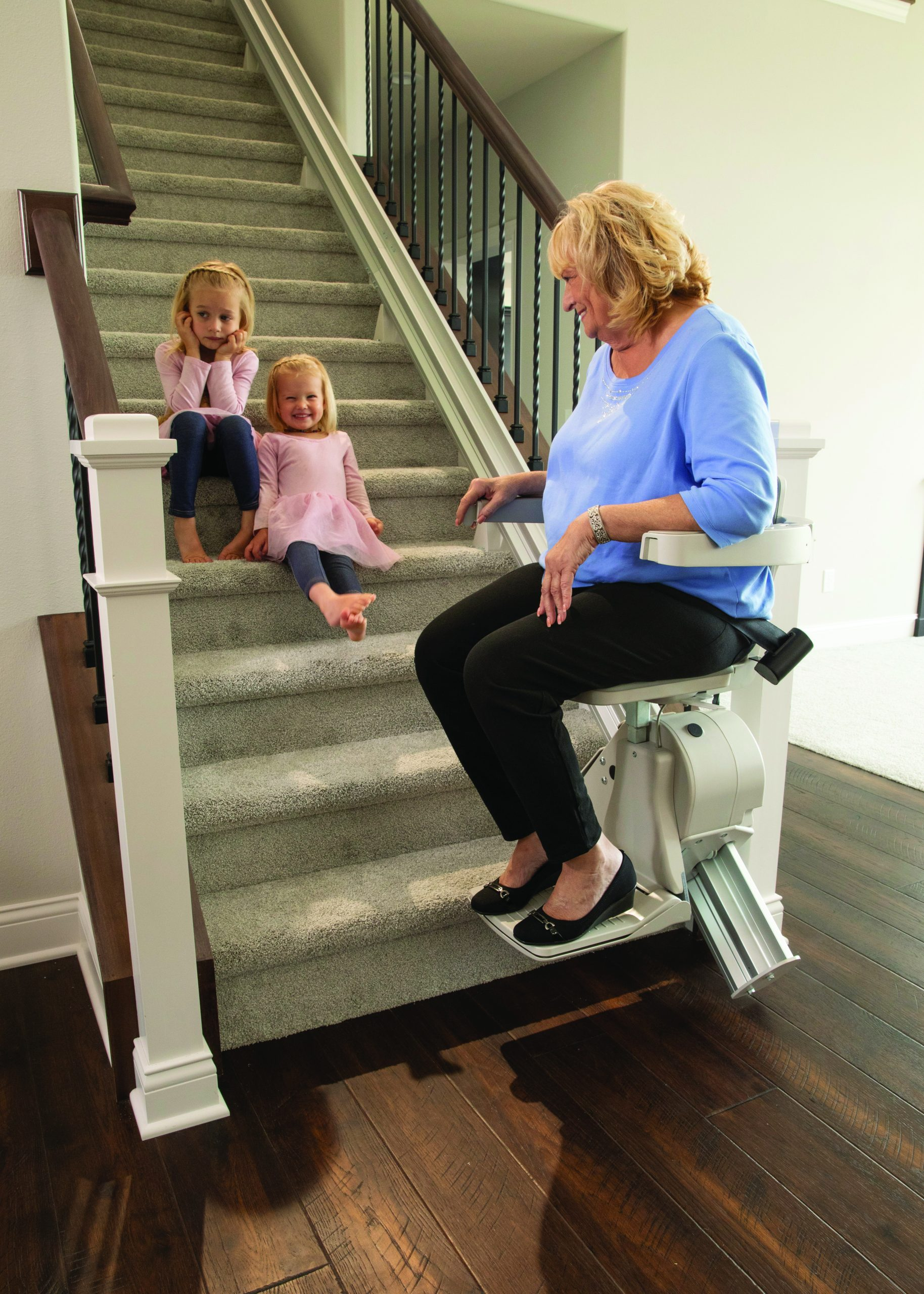 Grandmother using Bruno elan stair lift looking at grandchildren on stairs