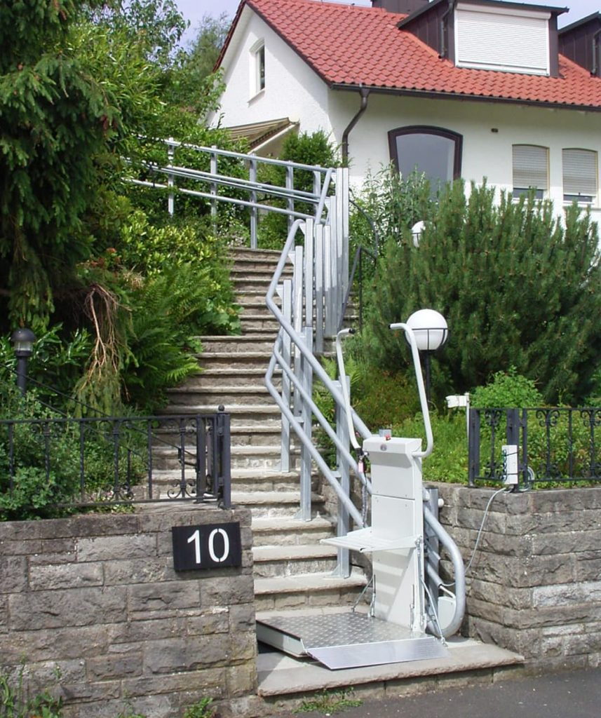 A platform lift leading up outdoor stairs to a house