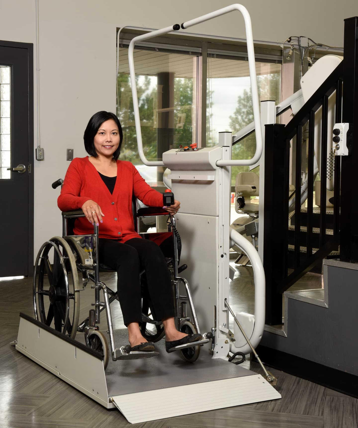 A woman in a wheelchair using a platform lift on stairs