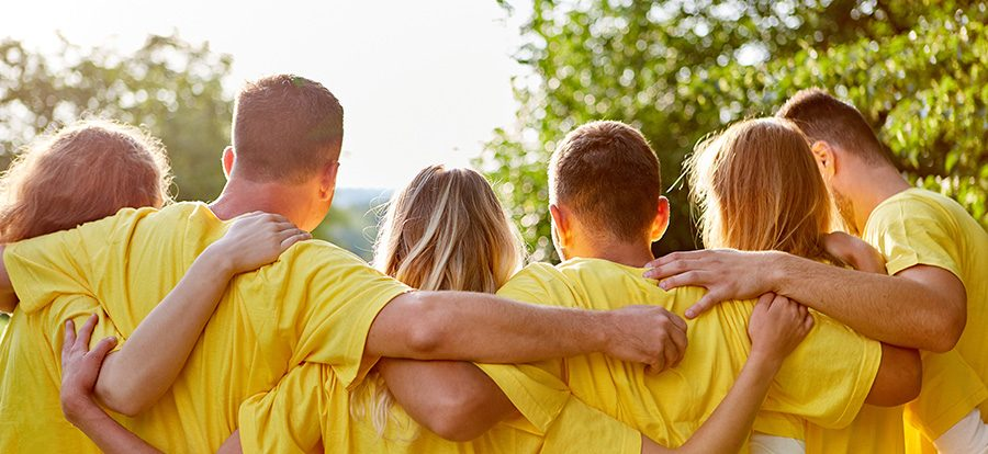 Young strong team hugs each other at a team building event in nature